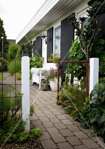 Offenes Gartentor und gepflasterter Weg entlang eines Wohnhauses, davor weisse Sitzbank