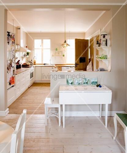 Blick vom Essplatz in die offene Küche mit ländlichem Flair, an Brüstungswand weisser Klapptisch