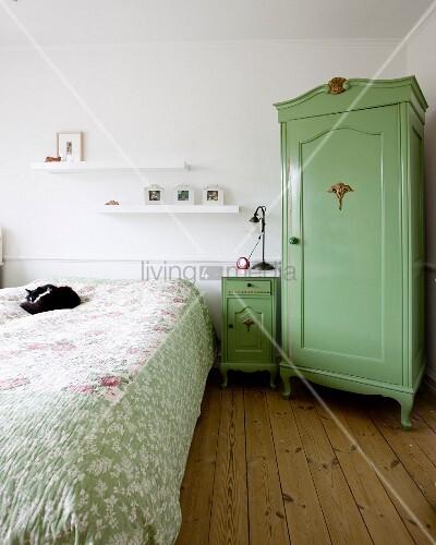 Bäuerlicher Eckschrank grün lackiert, neben Nachtkästchen und Doppelbett mit Katze auf Tagesdecke