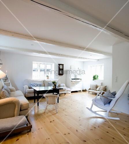 Weisser Schaukelstuhl in Loungebereich mit Sofas und schwarzem Tisch, Dielenboden
