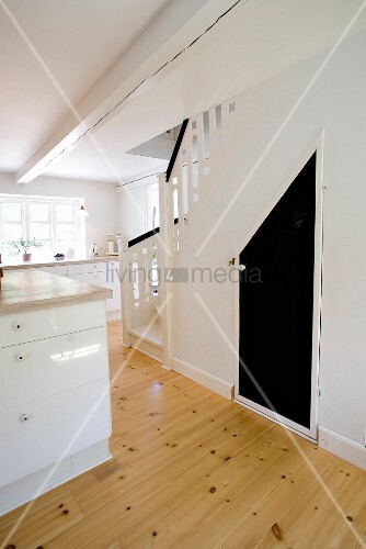 Open-plan kitchen with counter, white base units, staircase to one side and black door leading to under-stair storage space