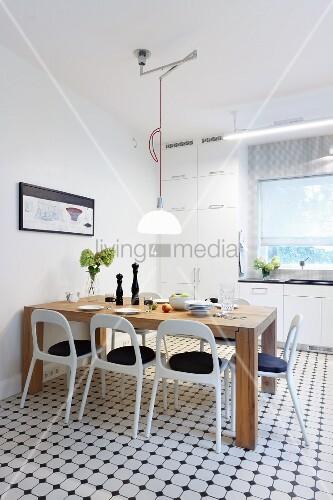 Massiver Holztisch und weisse Retro Stühle in moderner Küche mit ...