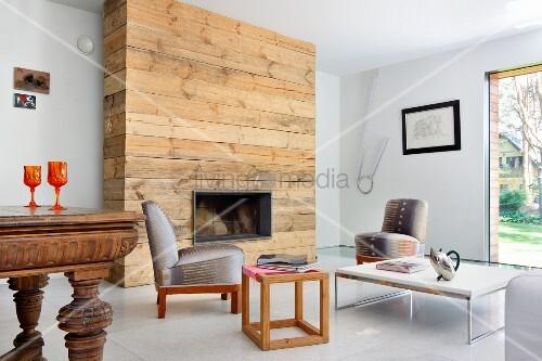 Rustikale naturbelassene Holzverkleidung der Kaminwand im Stilmix mit Retro Polsterstühlen und unterschiedlichen Tischen