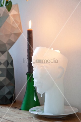 aus wachs geformter kopf als kerze neben kerzenhalter mit brennender kerze bild kaufen. Black Bedroom Furniture Sets. Home Design Ideas
