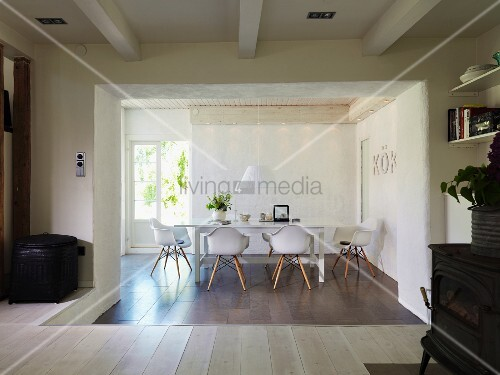 Sunken dining area with tiled floor, designer chairs and open terrace doors in renovated country house