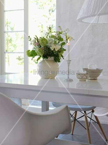 Romantic arrangement of lit candle and vase of flowers on glossy white table in front of open terrace doors