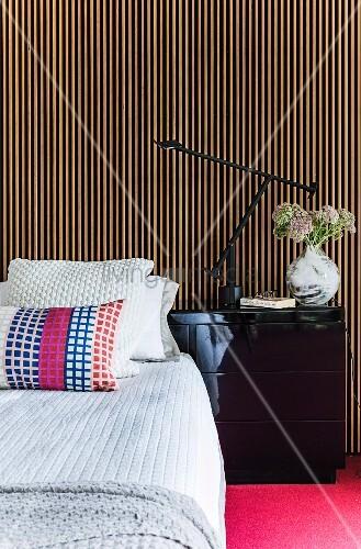 kissen auf bett mit tagesdecke seitlich schwarzer nachttisch vor wand mit. Black Bedroom Furniture Sets. Home Design Ideas