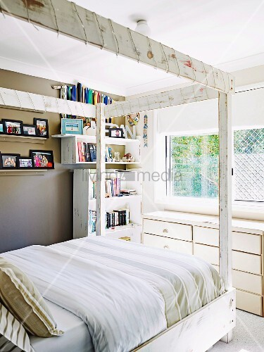 Four-poster bed decorated with fairy lights, bookshelves and family photos displayed on brown-painted wall