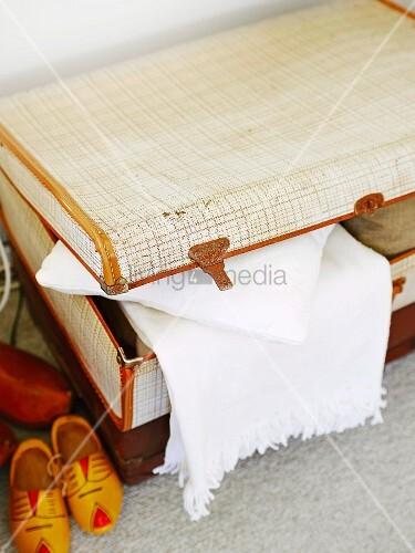 Heller Vintage Koffer mit weißem Plaid und Holzschuhen auf Teppichboden platziert