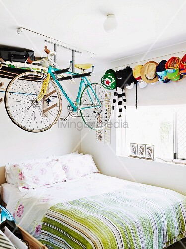 Racing bicycle hung from shelf above bed in teenager's bedroom with collection of peaked hats on wall