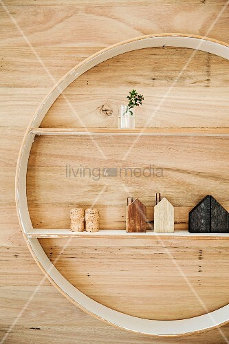 Round shelving unit with white shelves mounted on wood-clad wall and decorated with wooden house ornaments