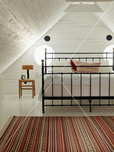 Striped rug in front of double bed with black metal frame in wood-clad niche in attic