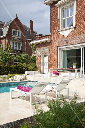 Sonnenliegen am modernen Pool eines traditionellen, belgischen Backsteinhauses mit weissen Zierelementen an den Fenstern