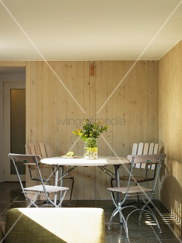 Round table and garden chairs in corner of wood-clad room