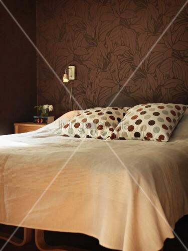 Kissen mit Punktemuster und helle Tagesdecke auf Doppelbett, vor tapezierter Wand mit floralem Muster auf braunem Untergrund