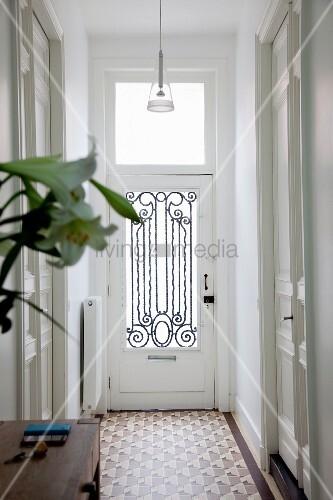 Blick auf Haustür mit verziertem, schmiedeeisernem Gitter in der Glasfüllung