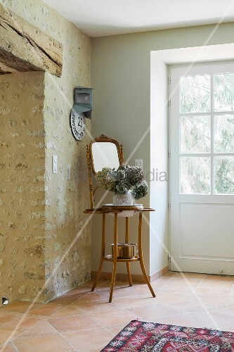 Foyer with stone wall, lattice front door and hydrangea and mirror on plant stand in corner