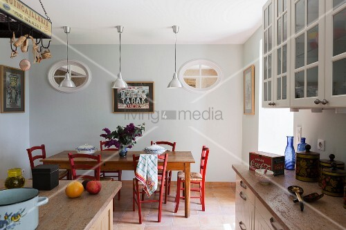 Dining area with red-painted kitchen chairs below row of pendant lamps in rustic kitchen