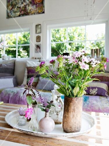 Gartenblumenstrauss und verschiedene Vasen mit Blumen auf Tablett