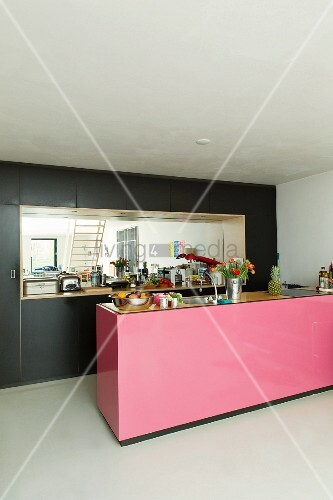 Pink Kitchen Island In Front Of Black Ed Cupboards With Mirrored Niche