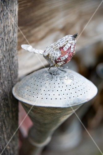 Hand-crafted bird ornament made from wire and newspaper on watering can rose