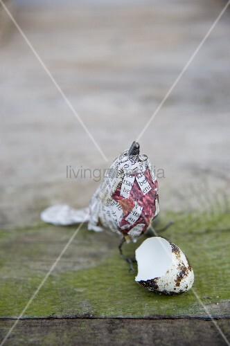 Eggshell in front of bird ornament made from wire and newspaper