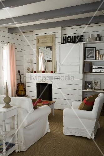 Polstersessel mit weisser Husse in Wohnzimmerecke mit weisser Holzverschalung vor Kamin