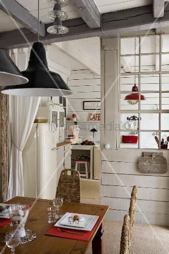 Esstisch aus Holz, oberhalb Pendelleuchten, im Hintergrund Trennwand vor Küche mit Sprossenverglasung