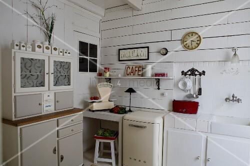 Retro Anrichte neben Küchenzeile in weisser, holzverschalter Küchenecke