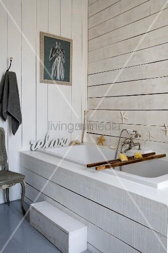 Eingebaute Badewanne mit weisser Holzverkleidung an Frontseite und an Wänden