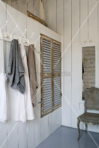 Towels Hanging On Row Of Coat Hooks Next To Ed Wardrobe With Rustic Louvre Doors In White Wood Clad Parion