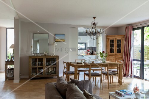 Open-plan interior with dining area in front of open sliding door with view into kitchen and sofa backrest in foreground