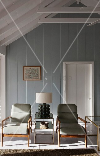 Lamp on mirrored table flanked by 50s retro armchairs in beach house painted grey and white with exposed roof structure