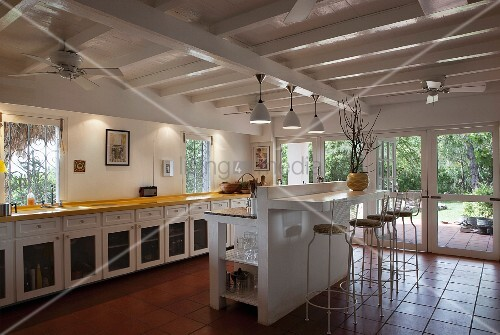 Long kitchen counter and masonry breakfast bar with wire stools below white-painted, wood-beamed ceiling