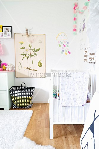 Vintage-style botanical illustration on wall above black and white patterned basket on floor next to white cot in nursery