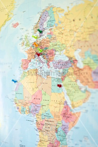 Drawing pins stuck into map of the world