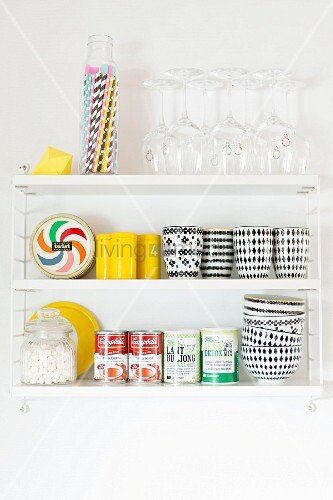 Black and white beakers and bowls, tinned food, glasses and drinking straws on white, wall-mounted shelves