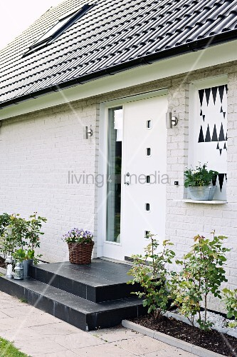 House with whitewashed brick façade, black steps and white front door flanked by narrow flowerbeds