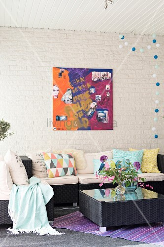 Dark rattan sofa and table, scatter cushions on sofa and modern artwork on whitewashed brick wall