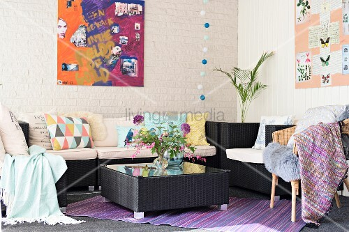 Dark rattan sofa and coffee table in corner, various scatter cushions and modern artwork on whitewashed wall