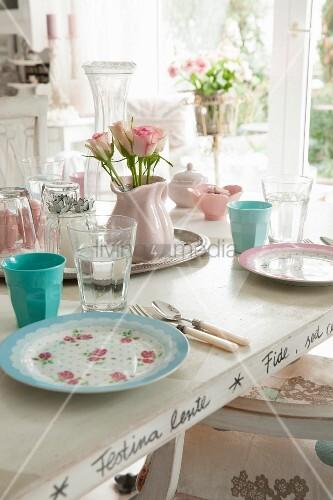 Romantisch gedeckter Tisch mit pastellfarbenem Geschirr