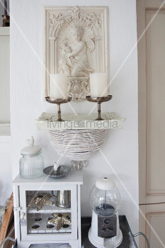 Small cabinet with chicken wire door, vintage gumball machine and candlesticks in front of relief panel on wall