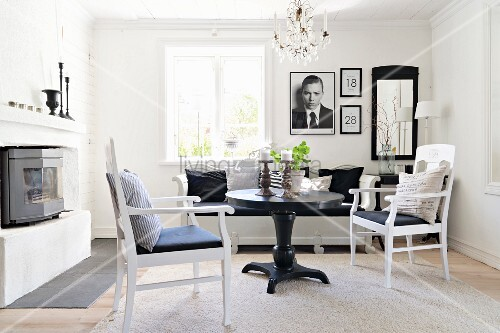 Black round table and white armchairs in comfortable living area
