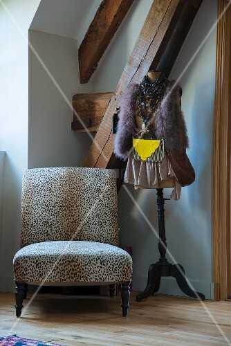 Leopard-print easy chair next to clothes on tailors' dummy in corner