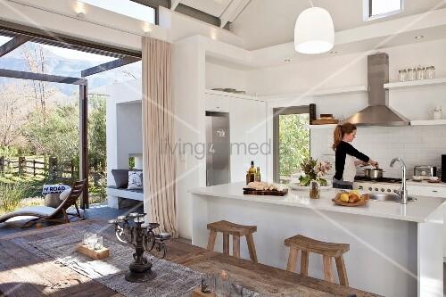 junge frau kocht in wei er offener k che mit k cheninsel offener terrassent r bild kaufen. Black Bedroom Furniture Sets. Home Design Ideas