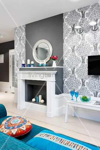 Elegant Grey And White Faux Fireplace Chimney Breast Flanked By Wallpaper With Pattern Of Stylised Trees Colourful Scatter Cushions On Blue Sofa In