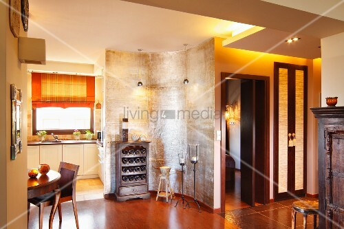 Shimmering, silver, curved partition and wine rack in front of modern fitted kitchen and dining area with Biedermeier table