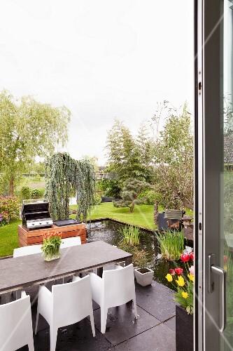 Blick von Terrasse mit modernem Edelstahl-Chassis Sitzplatz und ...