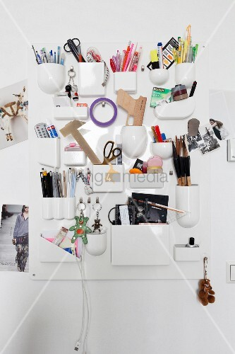 White organiser board with various pockets for storing drawing utensils and other objects