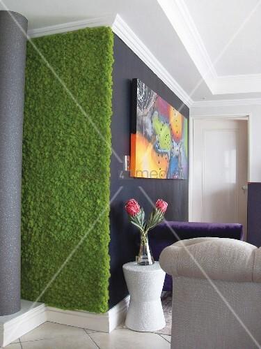 kunstrasenstreifen auf wand daneben weisser beistelltisch mit blumenstrauss vor schwarzer wand. Black Bedroom Furniture Sets. Home Design Ideas